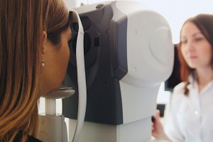 Ophthalmologist in eyes clinic doing diagnostic with vision for patient - high healthcare technology in medicine, de-focused