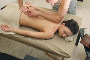 Half nude young female in massage table at spa salon - oil relax massage, spa concept - top view