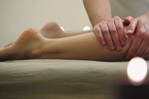Sesame oil massage for calf muscle. Relaxation treatment for young female, close up