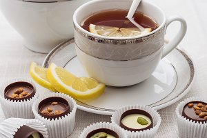 Sweets and tea with lemon on white.