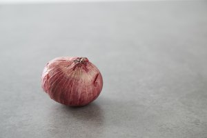 Red onion on gray stone background
