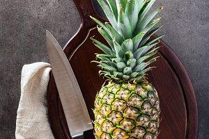 ripe pineapple on a cutting board