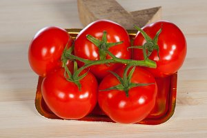 Five fresh red tomatoes with green stem in the tray , isolated on the background