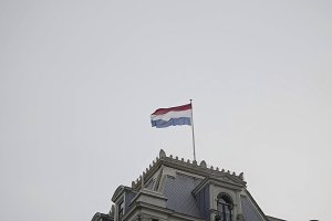Flag of netherlands on the top  building in front  the cloudy sky