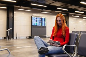 Young attractive woman with red hair and glasses use gadget in airport departure lounge
