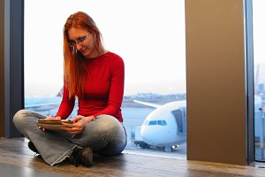 Young attractive woman with red hair and glasses use gadget near window in the airport