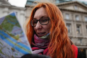 Yong tourist - woman with red hair and glasses looking map in Vienna