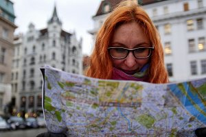 Young red hair woman using city map on square in Vienna, wide angle, close up