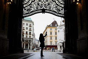 Woman using gadget in hofburg Vienna, silhouette, wide angle