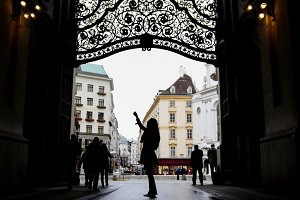 Woman using cell phone in hofburg Vienna, silhouette, wide angle