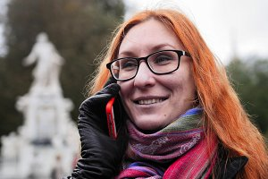 Young red hair woman using cell phone in Vienna, close up