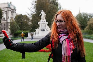 Young red hair woman using cell phone in Vienna, wide angle