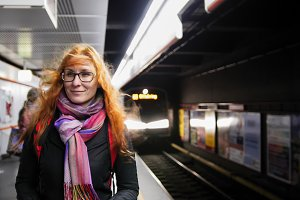 Beautiful young woman waiting subway at underground - train arrives