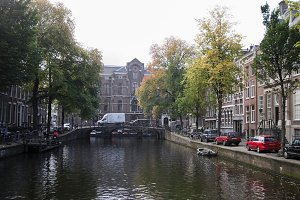 Amsterdam morning in center city - street with bicycles and cars on canal, Autumn, Netherlands