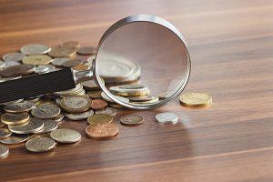 Different coins with a magnifying glass on the wooden table