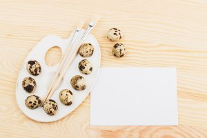 Quail eggs and different decorations, wooden background