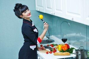 Girl cuts lemon in kitchen.
