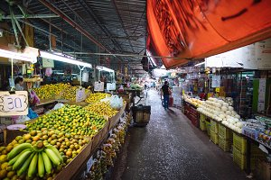 Bangkok food market with trays full of exotic Asian fruits - bananas, oranges, mangoes, papaya, Asia, Thailand