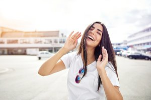 Laughing woman with hands up standing in street