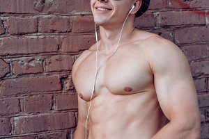 A happy male athlete, smiling in fresh air wearing a hat and glasses, with a smartphone and headphones listening to music, a fun outdoor recreation, an inflated bodybuilder in summer at wall, a vertical concept, a creative lifestyle.