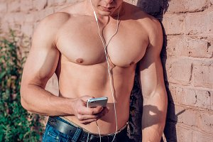 A man is an athlete, wearing a hat and glasses, wearing a hat and glasses, with a smartphone and headphones listening to music, an inflated bodybuilder in summer wall, vertical concept, creative lifestyle. Serious look
