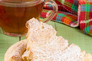 two puff cookies with a cup of tea on a green wooden background