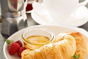 Freshly baked croissants with honey and jam