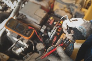 Mechanic works with car electrics - electrical wiring, voltmeter
