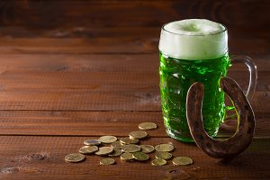 Beautiful background for St. Patrick's day with a glass of green beer, gold coins and a horseshoe on a wooden table. Free space
