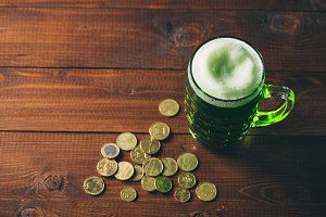 Beautiful background for St. Patrick's day with a glass of green beer and gold coins on a wooden table. Free space