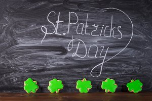 Beautiful background for St. Patrick's day with ginger leaf clover on a wooden table.