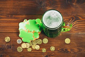 Beautiful background for St. Patrick's day with a glass of green beer, gold coins and gingerbread clover on a wooden table. Free space