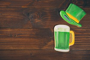 Beautiful background for St. Patrick's day with ginger glass of green beer and hat on a wooden table. Free space