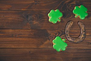 Beautiful background for St. Patrick's day with ginger clover and a horseshoe on a wooden table. Free space