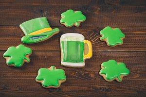 Beautiful background for St. Patrick's day with ginger clover, hat and a glass of green beer on a wooden table. Free space