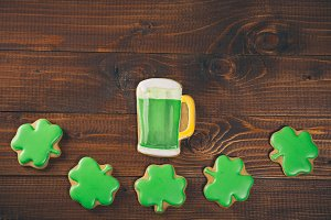 Beautiful background for St. Patrick's day with clover gingerbread and a glass of green beer on a wooden table. Free space