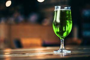 Glass of fresh cold green beer on a wooden bar counter in pub with free space for your text. Beautiful background of the Oktoberfest and St. Patrick's day. fine grain. Soft focus. Shallow DOF
