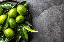 Green lemon Lime with fresh leaves on black plate, slate background