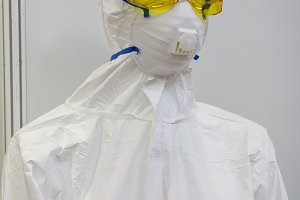 Mannequin in white protective clothing, respirator and plastic glasses