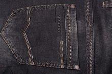 back pocket of dark jeans close up