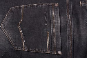 back pocket of dark jeans close up
