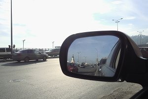 View in rear view mirror of city street traffic