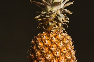 Pineapple is on the table  a dark background