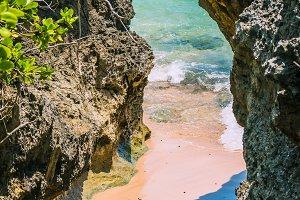 Small hidden Beach between Rockes covered by Cactus on Geger Beach in Nusa Dua Bali