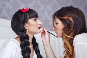 Visagist doing make-up bride.