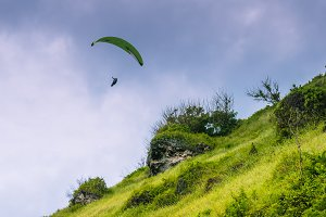 Paraglider flying off the Grassy Hills above Gunung Payung Beach, Bali