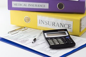 Clean insurance form, folders, pen and calculator