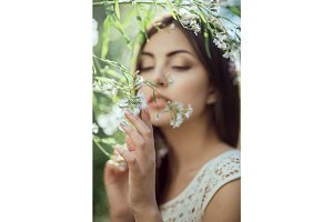 Wild flowers. Beautiful young woman portrait in flower field.