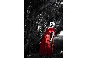 Woman in red dress in fairy forest.