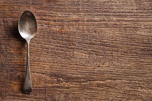 Rusty spoon on wooden table